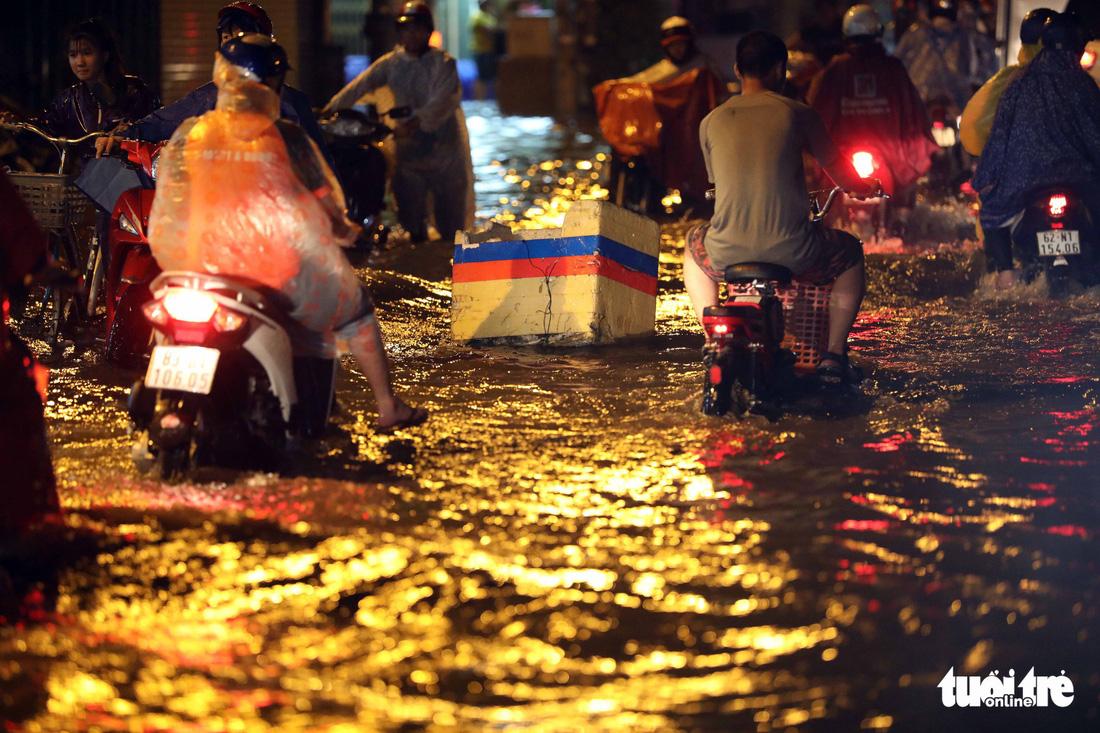 TP.HCM ngập nặng, người dân bì bõm dắt xe về lúc nửa đêm - Ảnh 7.