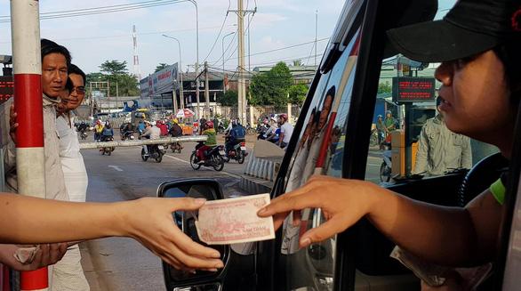 Tài xế buộc nhân viên thu phí nhận tiền lẻ, quốc lộ 1 kẹt cứng - Ảnh 1.
