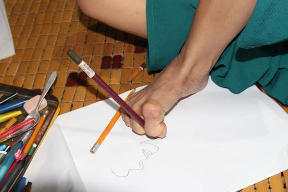 Cô gái miệt mài vẽ tranh bằng chân - Ảnh 1.