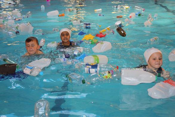 Trường cho học sinh bơi trong bể ô nhiễm để dạy về rác nhựa - Ảnh 1.
