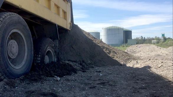 Sau khi đổ rác, xe ben đổ đất để san phẳng. (Ảnh: Internet)
