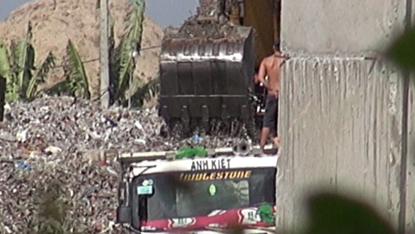 Xe ben đang được xe máy xúc múc từng gầu rác lên xe tại bãi tập kết huyện Nhà Bè, TP.HCM . (Ảnh: Internet)