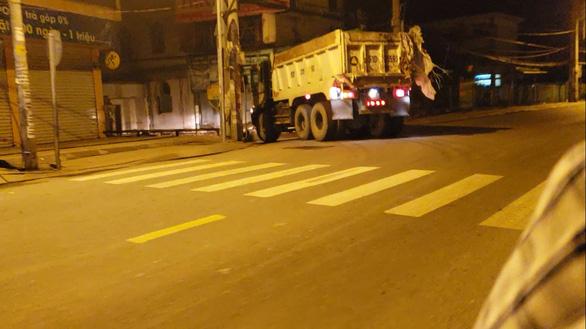Xe ben chở đầy rác đang rời bãi tập kết tại huyện Nhà Bè tiến về bãi đất tại xã Phong Phú, huyện Bình Chánh đổ xuống. (ảnh: Internet)