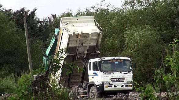 Xe ben  khi rời bãi tập kết tại huyện Nhà Bè đã đến bãi đất trống huyện Bình Chánh đổ rác san lấp mặt bằng.(Ảnh: Internet)