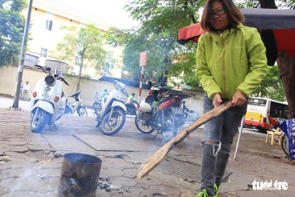Không khí lạnh tăng cường, dân Hà Nội bắt đầu đốt củi sưởi ấm - Ảnh 1.