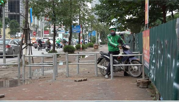 Hà Nội dựng rào chắn trên vỉa hè, dân đi ngược chiều dưới lòng đường - Ảnh 5.