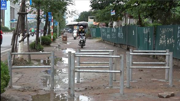 Hà Nội dựng rào chắn trên vỉa hè, dân đi ngược chiều dưới lòng đường - Ảnh 6.