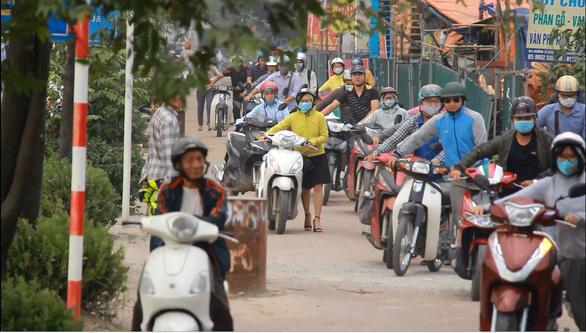 Hà Nội dựng rào chắn trên vỉa hè, dân đi ngược chiều dưới lòng đường - Ảnh 10.