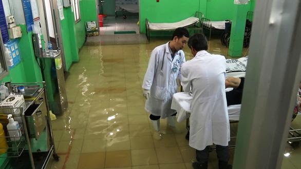 Bác sĩ lội bì bõm cứu bệnh nhân - Ảnh 1.