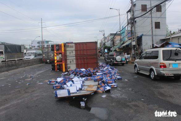 Xe container chở bia lật ngang, dân giúp tài xế gom bia - Ảnh 1.