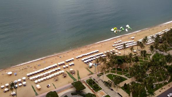 Giảm đặt dù trên bãi biển Nha Trang - Ảnh 1.