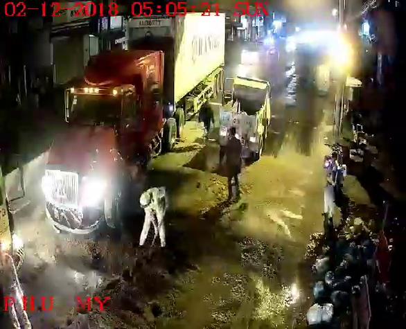 Cảnh sát giao thông rải cát lấp chỗ dầu nhớt tràn sau tai nạn - Ảnh 2.