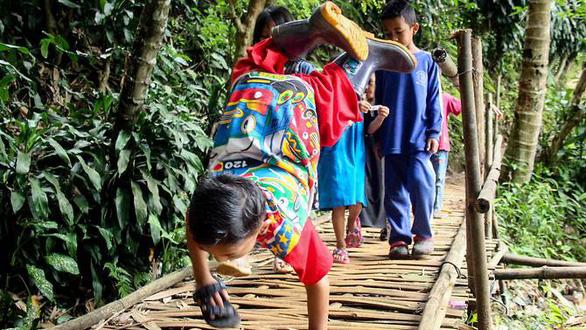 Cậu bé khuyết tật 'trồng chuối' đi học gây sốt ở Indonesia - Ảnh 1.