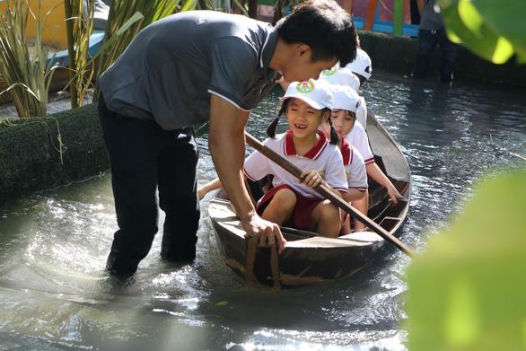 Học sinh Sài Gòn cười tít mắt khi đi xuồng trong... trường học - Ảnh 2.