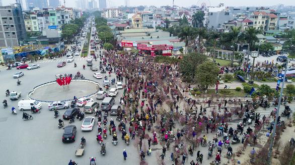 Dân Hà Nội đổ xô ra chợ hoa mua đào chơi Tết - Ảnh 8.