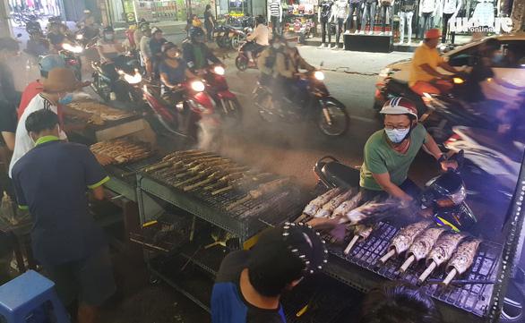 Phố cá nướng nhộn nhịp thâu đêm trước ngày vía Thần Tài - Ảnh 1.