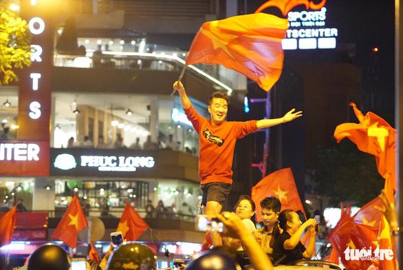 Mỹ Tâm, Đàm Vĩnh Hưng cầm cờ đi bão mừng chiến thắng U-23 VN - Ảnh 2.