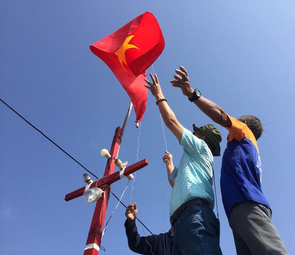 Tặng ngư dân cờ Tổ quốc mới trước khi ra khơi ở Hoàng Sa - Ảnh 1.