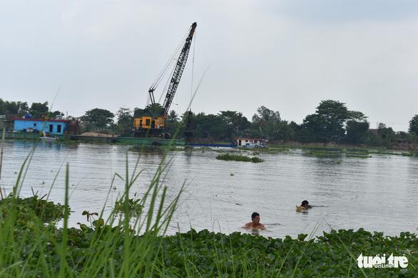 Dân ôm cây chuối bơi ra sông Hậu đấu xáng cạp - Ảnh 1.