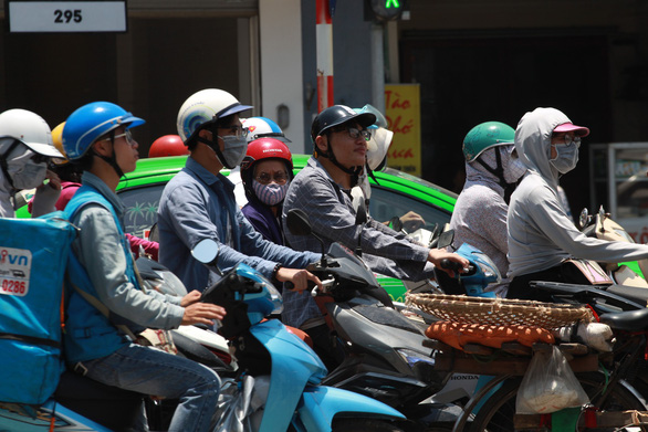 Dân Hà Nội như Ninja trong nắng nóng đầu mùa - Ảnh 2.