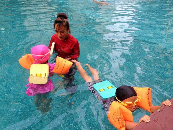 Nghỉ hè, cha mẹ trẻ đua nhau cho con đi học bơi - Ảnh 1.