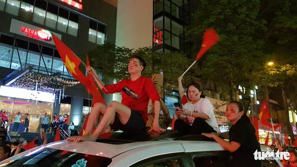 Mỹ Tâm, Đàm Vĩnh Hưng cầm cờ đi bão mừng chiến thắng U-23 VN - Ảnh 3.