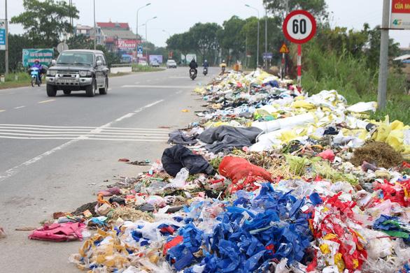 Hà Nội: Đổ trộm hàng đống rác ven quốc lộ, lấn nửa đường xe máy - Ảnh 1.