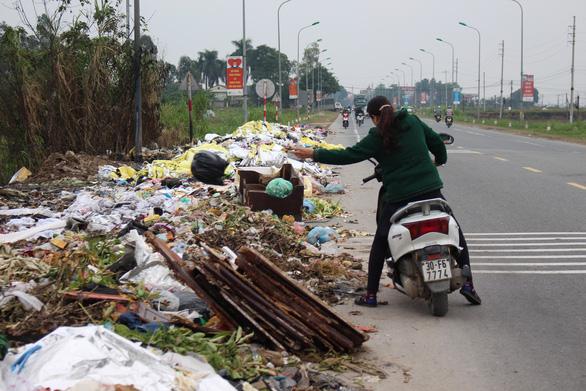 Hà Nội: Đổ trộm hàng đống rác ven quốc lộ, lấn nửa đường xe máy - Ảnh 2.