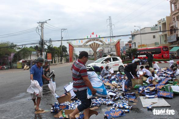 Xe chở bia đổ ra đường, dân xúm vào nhặt giúp tài xế - Ảnh 3.