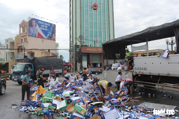 Xe chở bia đổ ra đường, dân xúm vào nhặt giúp tài xế - Ảnh 2.