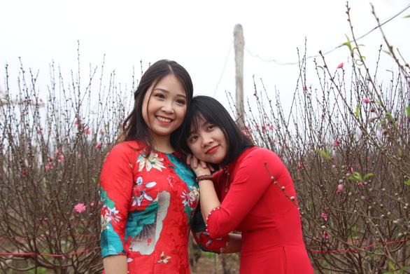 Thiếu nữ diện áo dài khoe sắc bên hoa đào đón tết Hà Nội - Ảnh 3.