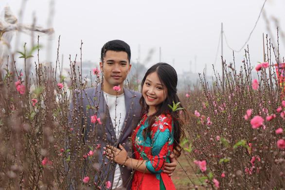 Thiếu nữ diện áo dài khoe sắc bên hoa đào đón tết Hà Nội - Ảnh 1.