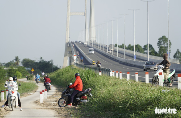 Mạo hiểm ngoặt đầu xe máy ngay chân cầu Cao Lãnh để vào đường tắt - Ảnh 1.
