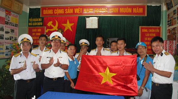 Chiến sĩ nhà giàn cổ vũ bóng đá với lá cờ có chữ ký đội tuyển - Ảnh 1.