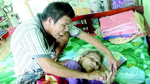 Người đàn ông thiểu năng nhặt ve chai nuôi mẹ già nằm liệt giường - Ảnh 1.