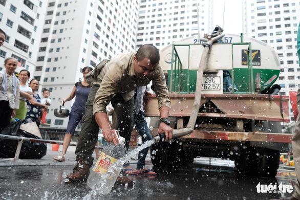 Xếp hàng lấy nước rồi đổ đi ngay vì nước không sạch - Ảnh 1.