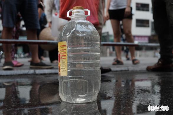 Xếp hàng lấy nước rồi đổ đi ngay vì nước không sạch - Ảnh 2.