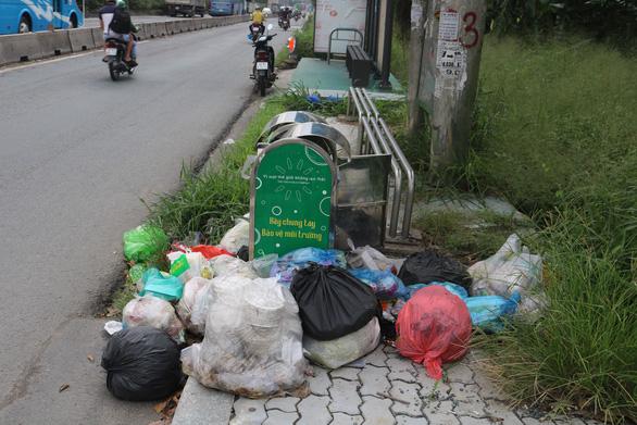 Trong khi chờ xe buýt thì tạm... ngửi mùi rác - Ảnh 1.