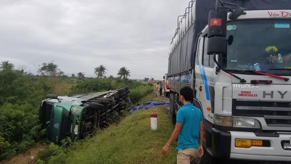 Hai xe tải lao xuống ruộng khi di chuyển trong bão nghi do mất lái - Ảnh 1.