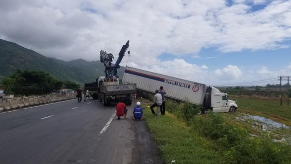 Hai xe tải lao xuống ruộng khi di chuyển trong bão nghi do mất lái - Ảnh 2.
