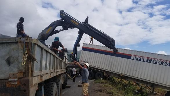Hai xe tải lao xuống ruộng khi di chuyển trong bão nghi do mất lái - Ảnh 3.