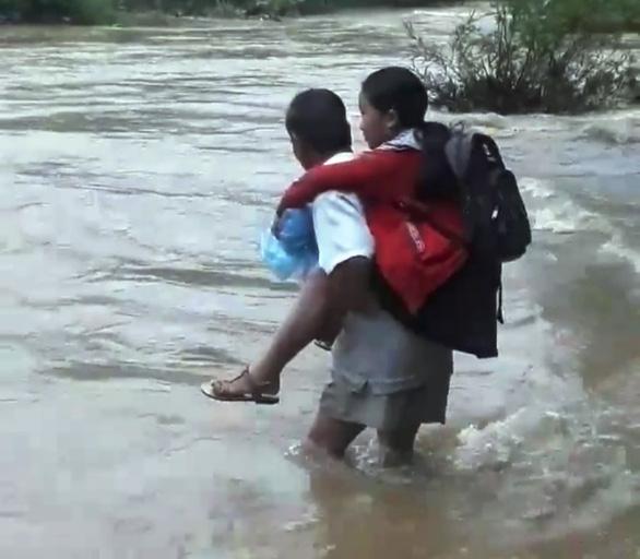Cha liều mình cõng con vượt dòng nước lũ cuồn cuộn đến trường - Ảnh 2.