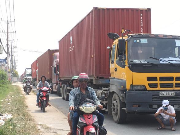 Container ùn ứ trên quốc lộ 13 vì hải quan tăng kiểm tra xuất xứ - Ảnh 1.