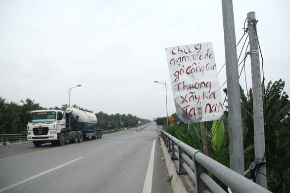 Dân tự làm biển báo cảnh báo tai nạn ở đường dẫn cầu Cổ Chiên - Ảnh 1.