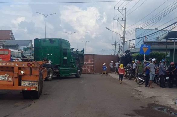 Thùng container rơi đè 2 vợ chồng trên quốc lộ 13 - Ảnh 1.