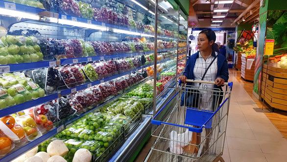 chị phượng (35 tuổi) đang chọn trái cây tại siêu thị co
