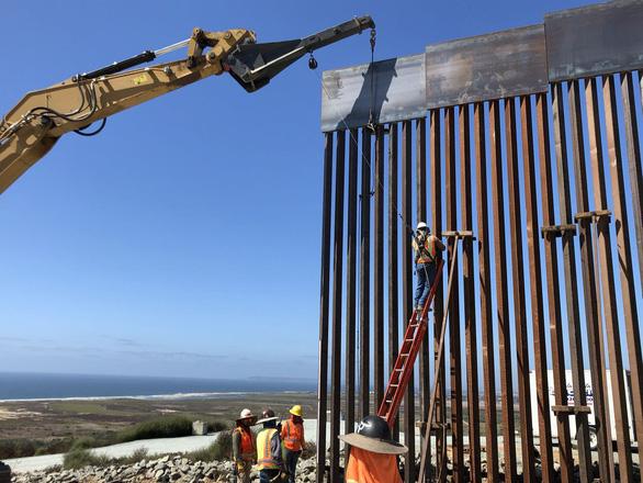 Tường biên giới Mỹ bị cưa chớp nhoáng - Ảnh 1.