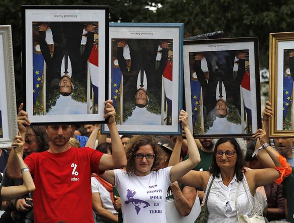 Pháp lúng túng xử phạt những người trộm áp phích in hình tổng thống Macron - Ảnh 1.