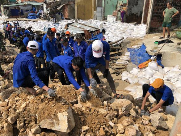 Thanh niên, bộ đội giúp dân dọn rác, vác đá vá bờ kè bị bão đánh sập - Ảnh 4.