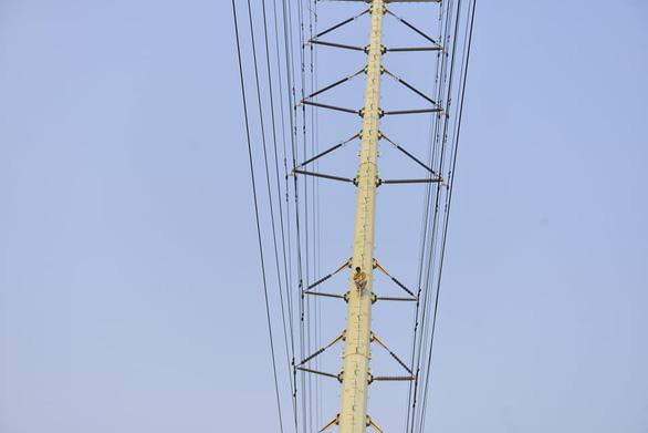 Cảnh sát đưa xe thang và đệm hơi ứng cứu thanh niên cố thủ trên cột điện cao thế - Ảnh 3.